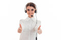 Pretty young brunette call office worker woman with headphones and microphone smiling and showing thumbs up on camera Royalty Free Stock Photo