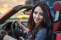 Pretty young brunette woman driving luxury red cabriolet car at the sunset. Royalty Free Stock Photo