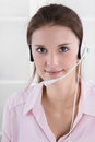 Pretty young business woman in rose blouse with headset. Royalty Free Stock Photo