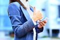 Pretty young business woman using mobile phone outdoor and ok sign Royalty Free Stock Photos