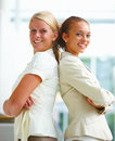 Pretty young business women standing back to back Royalty Free Stock Image