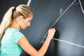 Pretty young elementary school college teacher writing on the chalkboard blackboa rd during a math class color toned image shallow Royalty Free Stock Photography