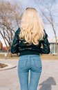 Pretty young fashion sexy girl with beautiful long blond hair on the road in evening summer time have fun and shows her nice back Royalty Free Stock Photo