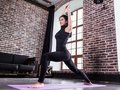 Pretty young female athlete in black sports outfit doing lunge exercise or standing in yoga low warrior pose on mat at