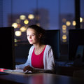 Pretty, young female college student using a desktop computer/pc Royalty Free Stock Photo