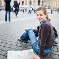 Pretty young female tourist studying a map Royalty Free Stock Photo
