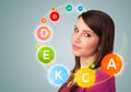 Pretty young girl with colorful vitamin icons and symbols on gradient background Stock Image