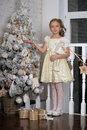 Pretty young girl dreaming of christmas with a sparkling tree behind Stock Photo