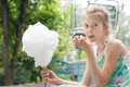 Pretty young girl eating a stick of candy floss picking at the sticky spun sugar with her fingers before placing it in her mouth Stock Photo