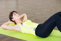 Pretty young girl fitness workout on mat in gym Royalty Free Stock Photo