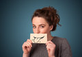 Pretty young girl holding white card with smile drawing on gradient background Royalty Free Stock Photo