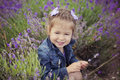 Pretty young girl sitting in lavender field in nice hat boater with purple flower on it. Royalty Free Stock Photo