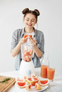 Pretty young girl smiling blending detox refreshing grapefruit smoothie over white wall. Healthy food concept.