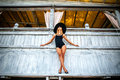 Pretty young girl standing near wooden wall in black swimwear Royalty Free Stock Photo