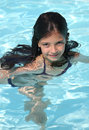 Pretty young girl in a swimming pool on hot day Stock Image