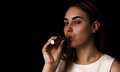 Pretty young girl uses electronic cigarette Royalty Free Stock Photo