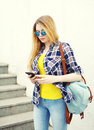 Pretty young girl wearing a sunglasses and backpack using smartphone Royalty Free Stock Photo