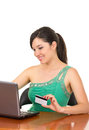 Pretty young happy girl sitting in front of her laptop buying online isolated on white Royalty Free Stock Photos