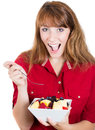 Pretty young happy redhead woman eating fruit salad portrait of a isolated on a white background Royalty Free Stock Photo