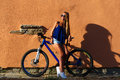 Pretty young hipster blonde girl posing with sport bicycle outdoor against wall nice colors sunset Royalty Free Stock Photo