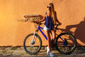 Pretty young hipster blonde girl posing with sport bicycle outdoor against wall nice colors sunset Stock Image