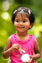 Pretty young indian girl kid having fun eating ice cream in a park the photo shows female child tiny tot smiling and enjoying her Stock Photo