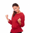 Pretty young lady celebrating her victory portrait of on red shirt with eyes closed on isolated studio Stock Images