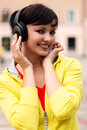 Pretty young lady listening to music in the park Stock Image