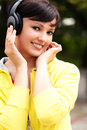Pretty young lady listening to music in the park Stock Images