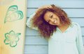 Pretty young lady smiling and leaning on surfboard portrait of a Royalty Free Stock Photo