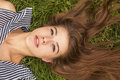 Pretty young long-haired girl lying on the green grass Royalty Free Stock Photo