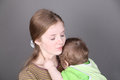 Pretty young mother holds her little baby son in green in grey studio Stock Photos