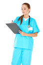 Pretty young nurse writing up notes in green scrubs standing on a clipboard with a serious expression isolated on white Royalty Free Stock Photo