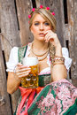 Pretty young oktoberfest blonde woman in a dirndl dress with beer