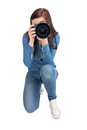 Pretty young photographer taking picture of camera against white background Royalty Free Stock Photography