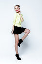 Pretty young playful girl dressed in green pullover and black skirt. Royalty Free Stock Photo