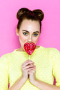 Pretty young playful girl holding heart-shaped lollipop Royalty Free Stock Photo