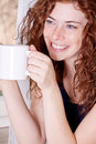 Photo : Pretty young redhead woman with freckles and coffe  camera
