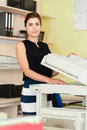 Pretty young secretary using a copy machine woman Royalty Free Stock Images