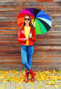 Pretty young smiling woman with colorful umbrella wearing a red leather jacket and rubber boots in autumn over wooden background Royalty Free Stock Photo