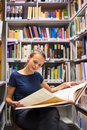 Pretty young woman in archives studying an old book Royalty Free Stock Photos