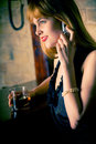 Pretty young woman at bar counter, on mobile phone Stock Images