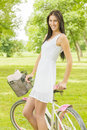 Pretty young woman with bicycle in the park at beautiful spring day Royalty Free Stock Photo