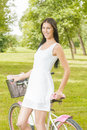 Pretty young woman with bicycle in the park at beautiful spring day Stock Photo