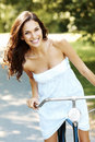 Pretty young woman with bicycle in a park smiling Royalty Free Stock Photos