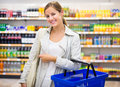 Pretty young woman buying groceries in a supermarket mall grocery store color toned image shallow dof Stock Photos