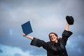 Pretty young woman celebrating joyfully her graduation spreading wide arms holding diploma savouring success color Stock Images