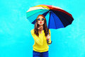 Pretty young woman with colorful umbrella sends air sweet kiss in autumn day over blue background wearing yellow knitted sweater Royalty Free Stock Photo