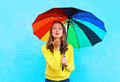 Pretty young woman with colorful umbrella sends air sweet kiss in autumn day over colorful blue background Royalty Free Stock Photo