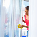 Pretty young woman doing house work washing windows shallow dof color toned image Royalty Free Stock Photo